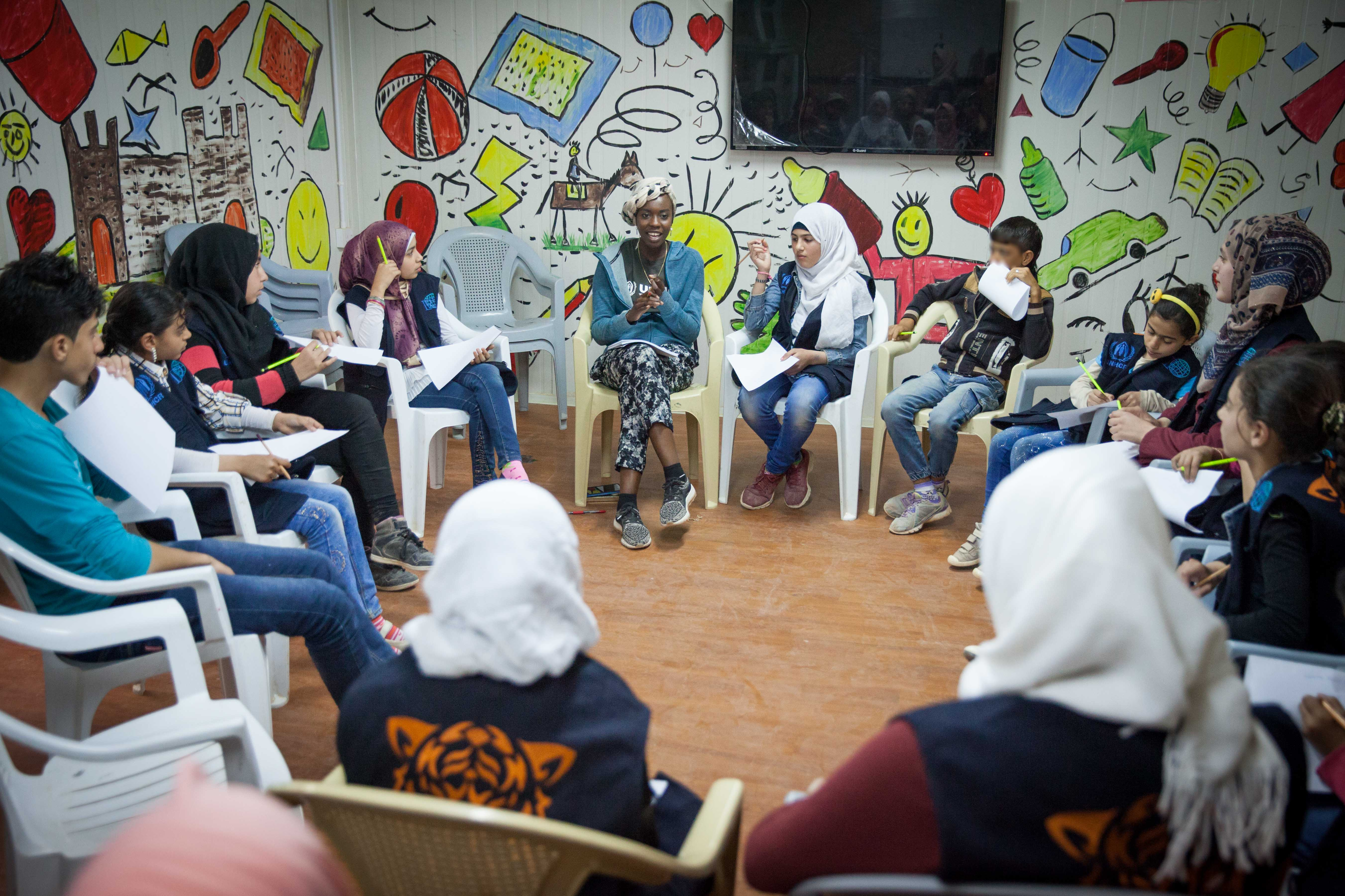 UNHCR High Profile Supporter Emi Mahmoud conducts a poetry workshop with girls and boys at the community center in Zaatari camp, Jordan. ; UNHCR High Profile Supporter Emi Mahmoud visists Syrian refugees in Jordan